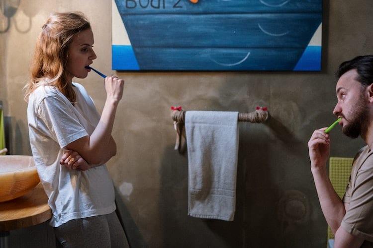 deux personnes se regardent en se brossant les dents