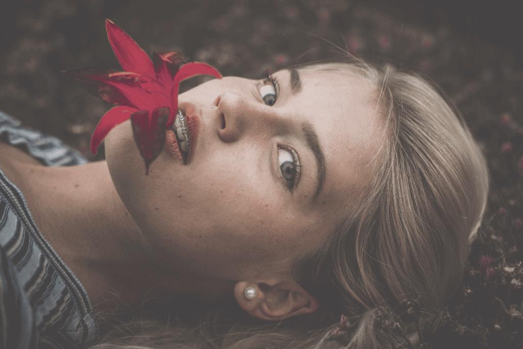 femme avec appareil allongé fleur dans la bouche